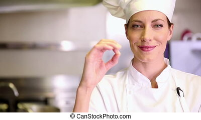 Pretty chef smiling at camera and giving thumbs up in...