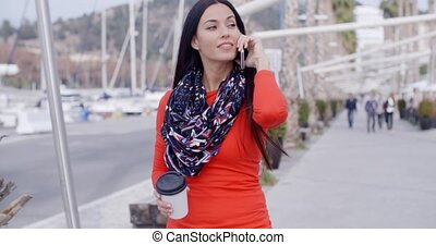 Pretty chic young woman chatting on a mobile