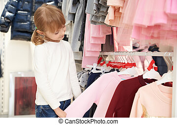 Pretty child choosing clothing in store.