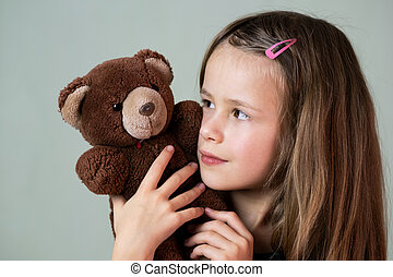 Pretty child girl playing with her teddy bear toy.