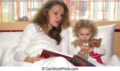 pretty child girl sit with two toy cats and listen for mother reading story
