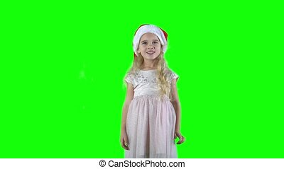 Naughty girl play-act simper with Christmas hat cap. Pretty child with curly blond hair. Chroma key green screen background