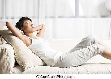 Pretty Chinese woman asleep at home on the sofa.