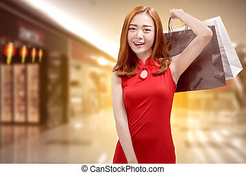 Pretty chinese woman in traditional dress carrying shopping bags