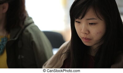 Pretty chinese woman sits at table in office with her colleagues.