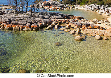 Pretty Coastal scene with turquoise waters rippled, rocky...