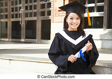 pretty college student holding a diploma at campus