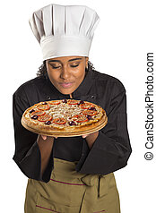 Pretty cook woman smelling pizza.