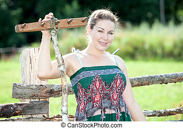 Pretty countrywoman standing with wooden rake behind fence in sundress