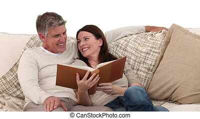 Pretty couple looking at an album on the sofa