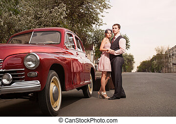 Pretty couple near the vintage car on the sunset background