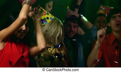 Pretty couple of young people dancing at a party in the spotlight. Slow motion