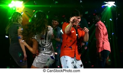 Pretty couple of young people dancing at a party in the spotlight