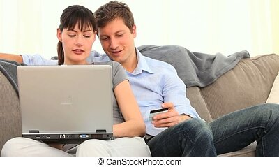 Pretty couple using a credit card on internet in the living...