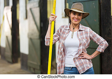 pretty cowgirl holding pitch fork inside stables