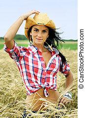 Pretty cowgirl in wheat field