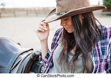 Pretty cowgirl leaning on fence at ranch - Close up portrait...