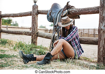 Pretty cowgirl resting while leaning on the ranch fence -...