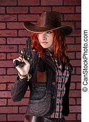 Pretty cowgirl with the revolver. Brick background.