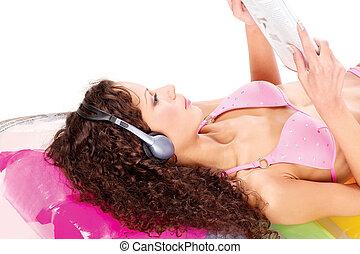 girl on air mattress reading newspaper - Pretty curl girl on...