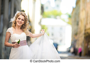 Pretty curly bride with a huge bow in her hair poses on the street