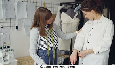Pretty customer is trying on tailored shirt and sharing her...