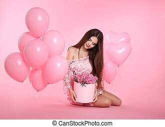 Pretty cute brunette girl with balloons and bouquet of rose flowers in hat box isolated on pink studio background. 8 march. Birthday party.