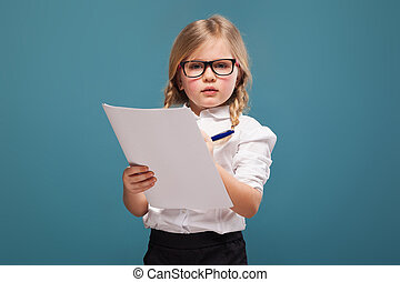 Pretty, cute little girl in white shirt, glasses and black trousers hold papers