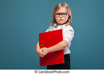 Pretty, cute little girl in white shirt, glasses and black trousers hold red paper folder