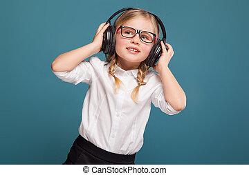 Pretty, cute little girl in white shirt, glasses, black trousers and headphones