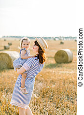 Pretty dark-haired woman in straw hat and striped dress holding her little blond daughter at sunset relaxing in the summer wheat field with hay bales on the background. Walk in the countryside