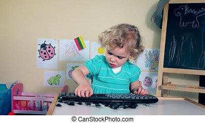 Pretty daughter girl destroying keyboard. Handheld steadycam...
