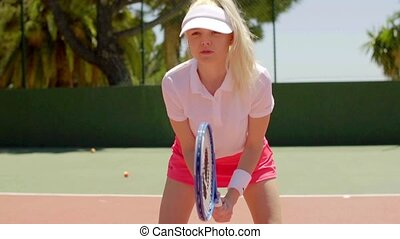 Pretty determined blond tennis player bending forward in...