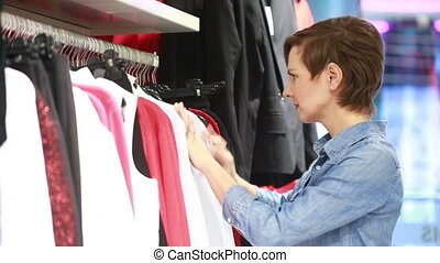 pretty elegant woman shopping in clothes store. Hanger with...