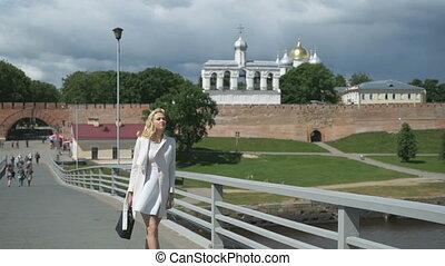 Pretty elegant woman walking along bridge