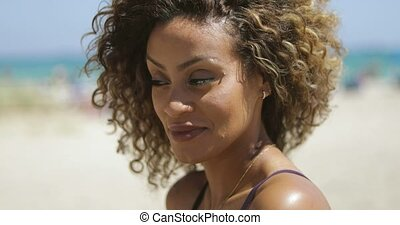 Pretty ethnic curly woman on shore - Portrait of confident...