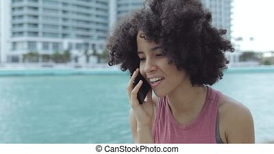 Pretty ethnic girl speaking on phone outside