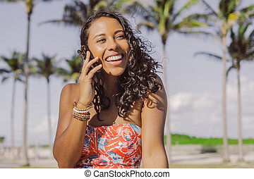 Pretty ethnic woman talking on smartphone in summertime