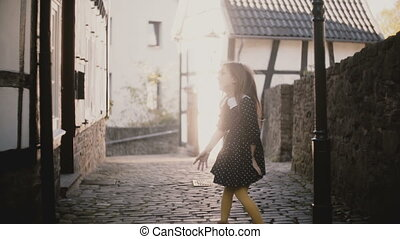 Pretty European girl throws air kisses, runs away. Excited female child posing, running from camera on paved road. 4K.