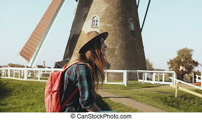 Pretty European tourist girl near old wind mill. Beautiful young woman in hat with long hair sits near village mill. 4K