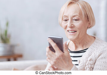 Pretty excited elderly woman texting on phone - Good news....