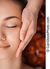 pretty face massage at the spa salon. girl laying on massage...