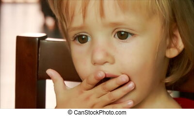 pretty face of little blonde girl eating long macarony
