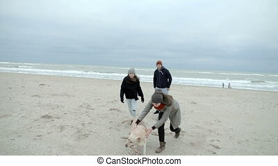 Pretty family is playing with a dog on the beach.