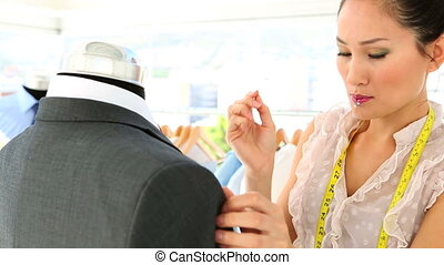 Pretty fashion designer adjusting suit in her studio