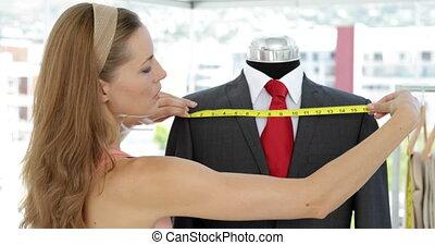 Pretty fashion designer measuring s