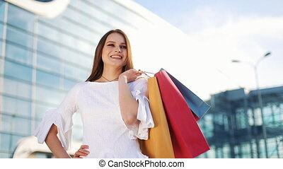 Pretty fashion model in white dress poses with shopping bags...