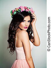 Pretty Fashion Model with Long Curly Hair and Flowers. Beautiful Brunette Woman in Summer Pink Dress