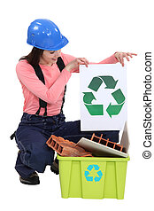 pretty female bricklayer holding recycling logo