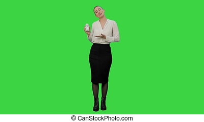 Pretty female businesswoman describing and advertising pills for the camera on a Green Screen, Chroma Key.